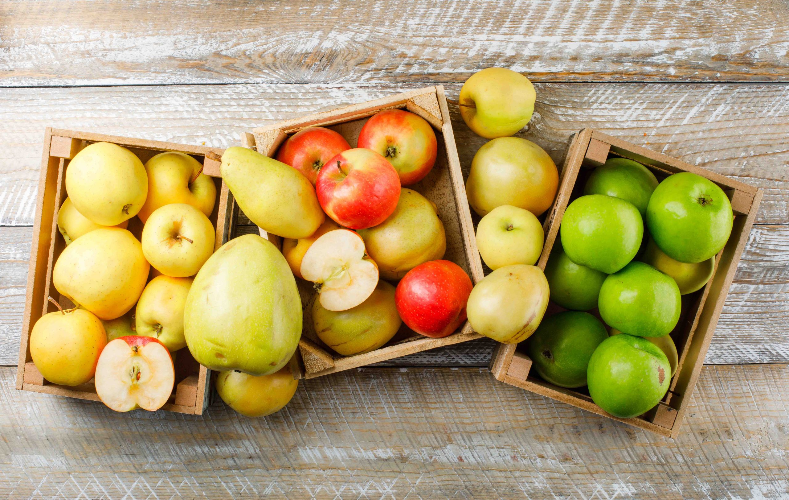 Apples variety with pears in wooden boxes on wooden background, top view.